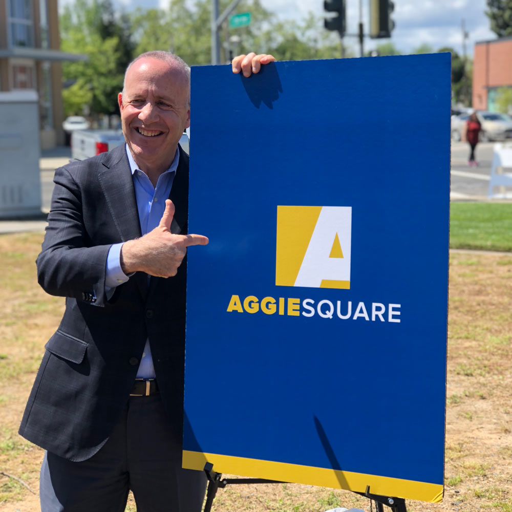 """A picture of a man pointing to a sign that says Aggie Square"""