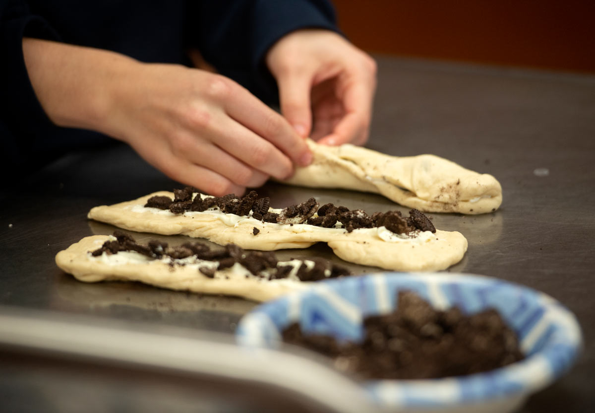 Hands work with three braids, adding Oreo cookie pieces.