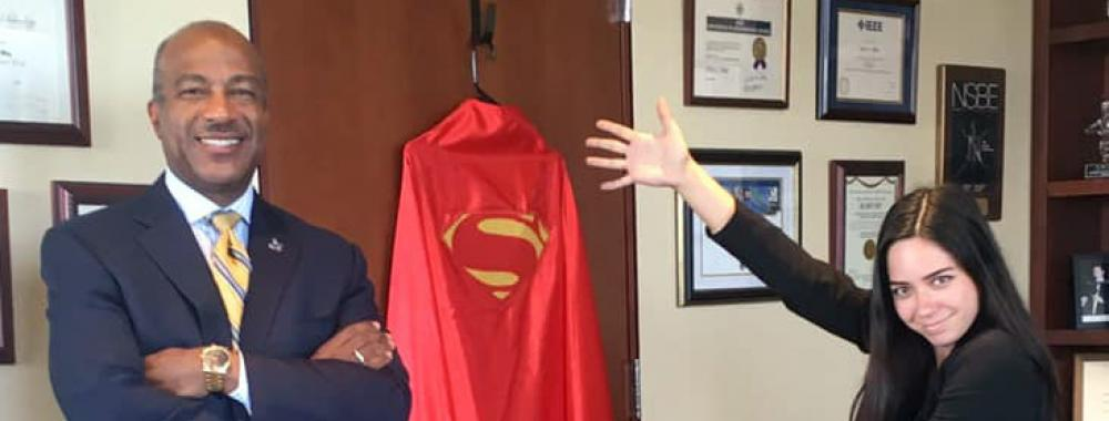 Teddy Cruz pointing to Chancellor Gary S. May's Superman cape.