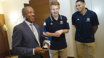 UC Davis men's basketball players Siler Schneider, Roger Printup and Chima Moneke (not pictured) and coach Jim Les (not pictured) visit Chancellor Gary May to give him his own Championship Basketball ring. The foursome visited the 5th floor of Mrak Hall on August 8, 2017.