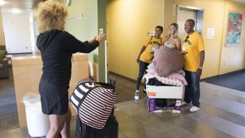Laurie Meyers takes a photo of her daughter, Lainey Hauschildt, with LeShelle and Gary May as they help her move into her room in the Tercero Residence Halls on Saturday, September 23, 2017. Hauschhidlt is a freshman from Sebastopol, CA.