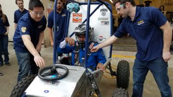 Chancellor May visits the College of Engineering Aggie Baja lab and takes their student designed racecar for a ride.