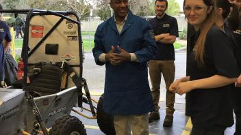 Chancellor May visits the College of Engineering Aggie Baja lab and prepares to take the student designed racecar for a ride.
