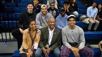 Chancellor May and his wife LeShelle May cheer on the women's basketball team with a group of student athletes.