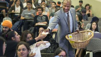 Chancellor May hands out cookies to the students in BIS 103 part of a surprise visit to award Professor Judy Callis the UC Davis Prize for Undergraduate Teaching and Scholarly Achievement.