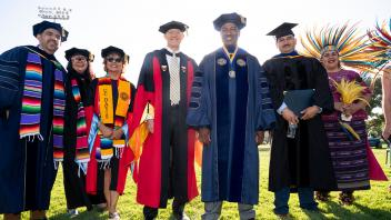 Chancellor Gary May poses with faculty members before the start of the Chicanx/Latinx Graduation Celebration at the Pavilion on June 15, 2018.