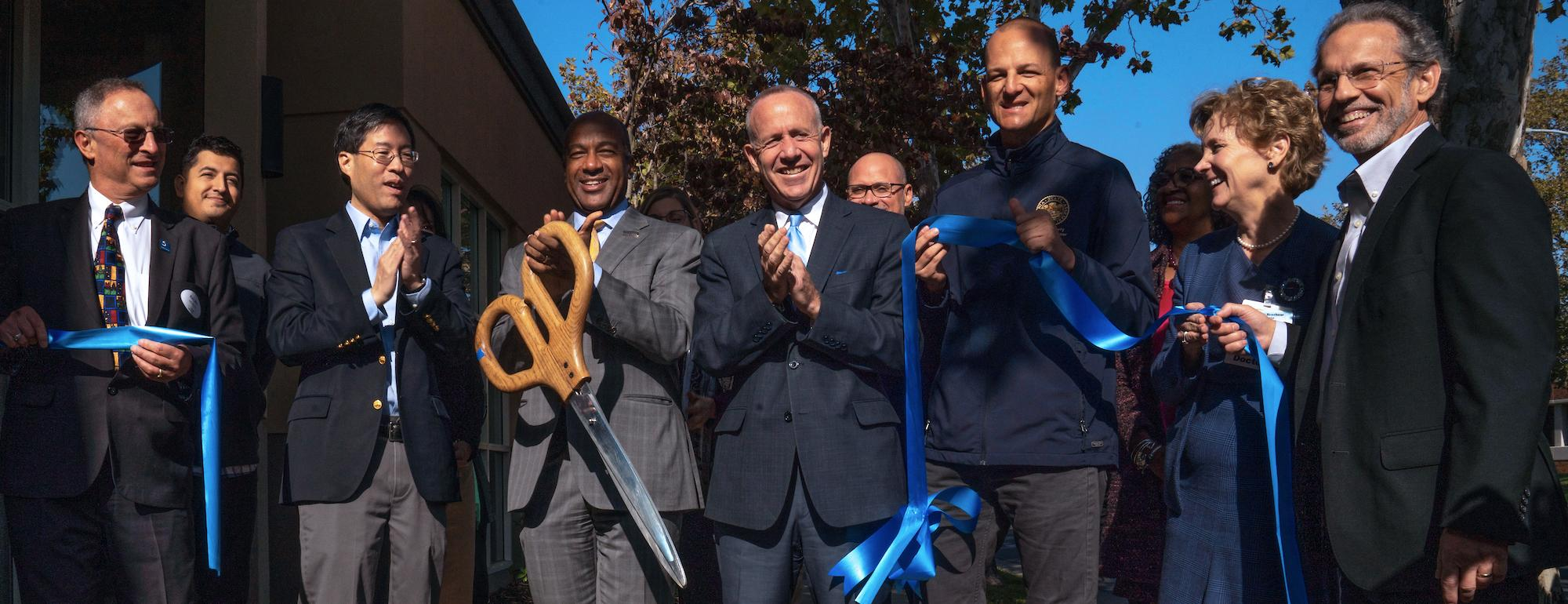 Chancellor Gary May and a team of people cut a ribbon at UC Davis Aggie Square