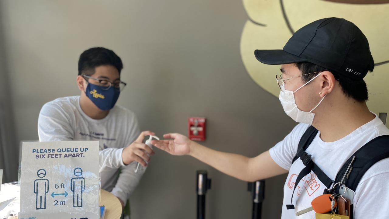 Masked public health ambassador providing hand sanitizer to student.