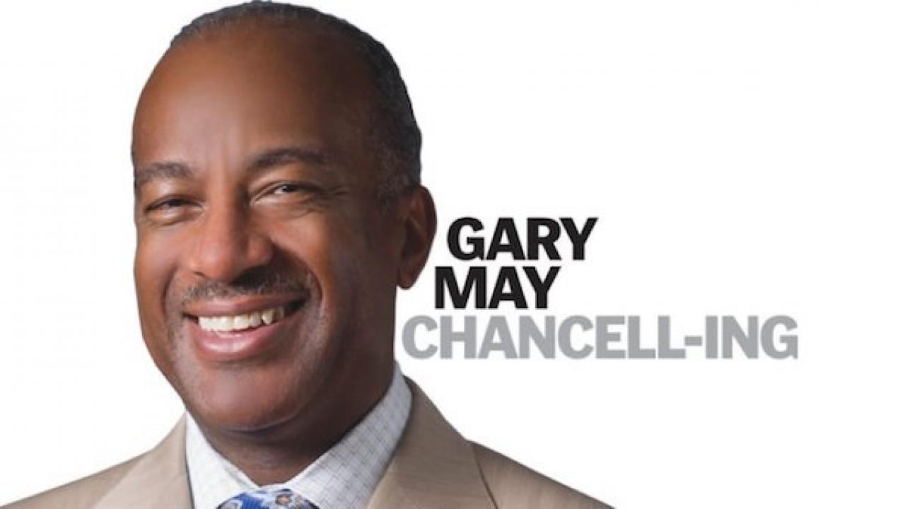 "Chancellor Gary May smiling, looking at camera on white background. Words ""Gary May Chancell-ing"" is overlaid on the white background."