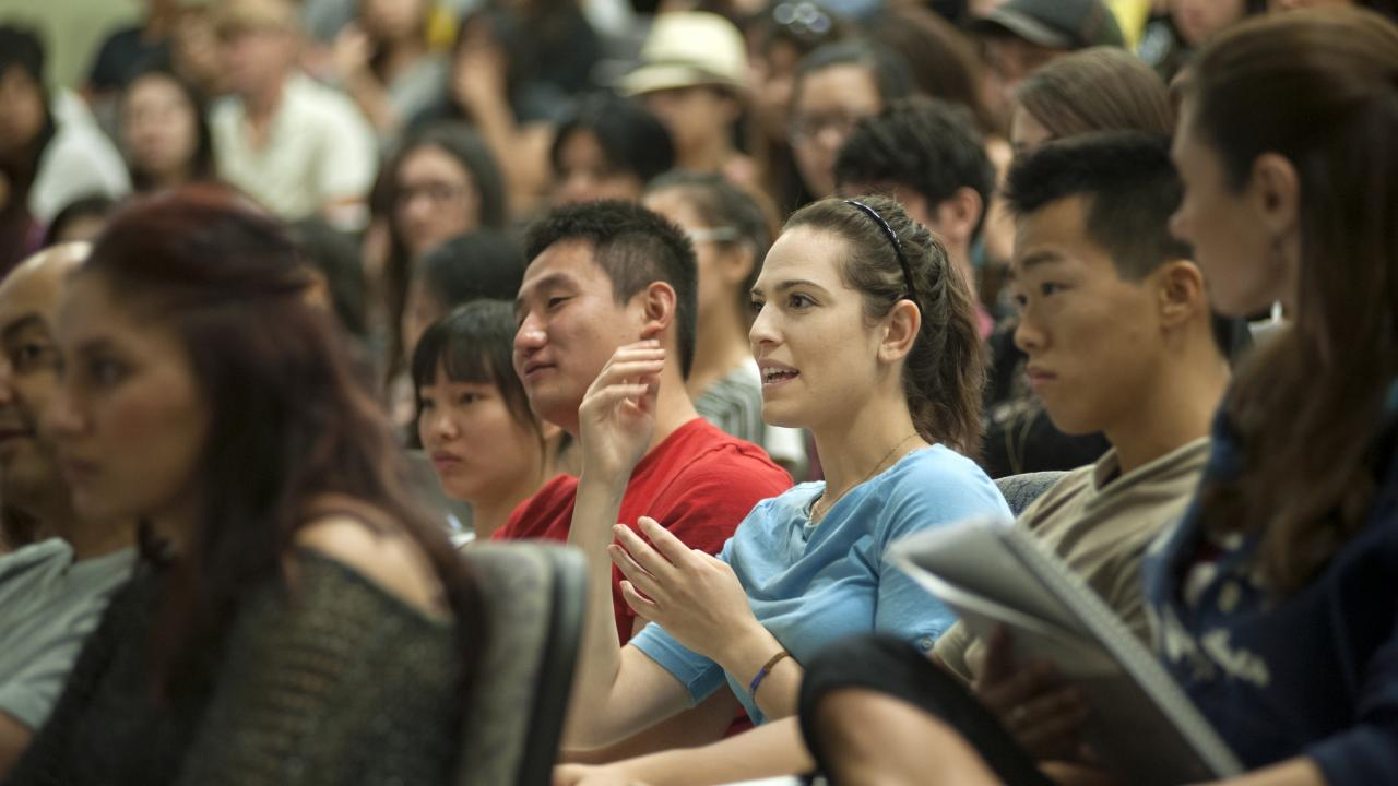 Female student in audience speaks in a large classroom at UC Davis