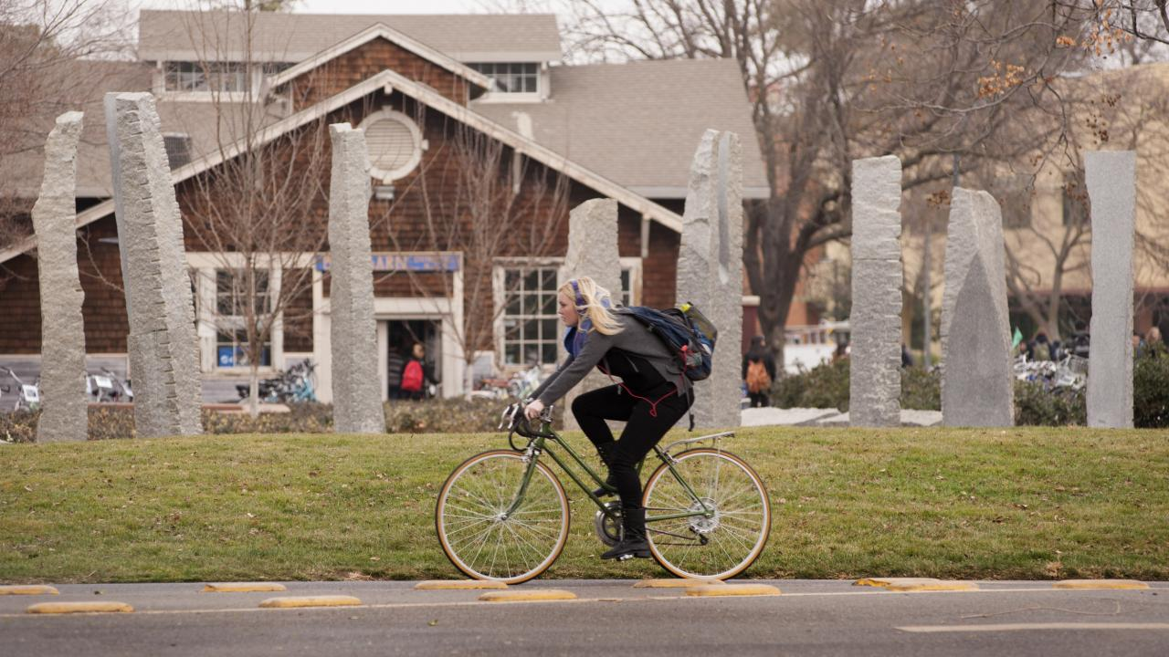 student riding bike in front of UC Davis Stone Poem sculpture