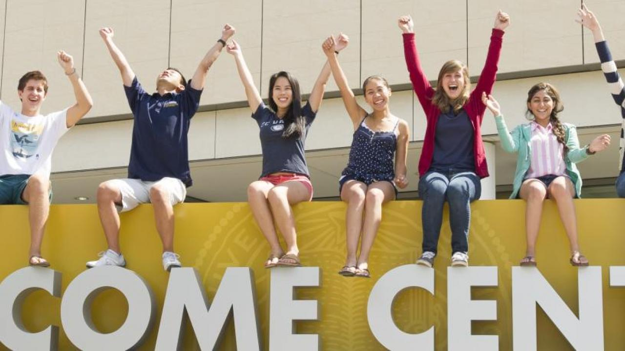 Students sit on top of giant letters reading WELCOME at UC Davis Welcome Center