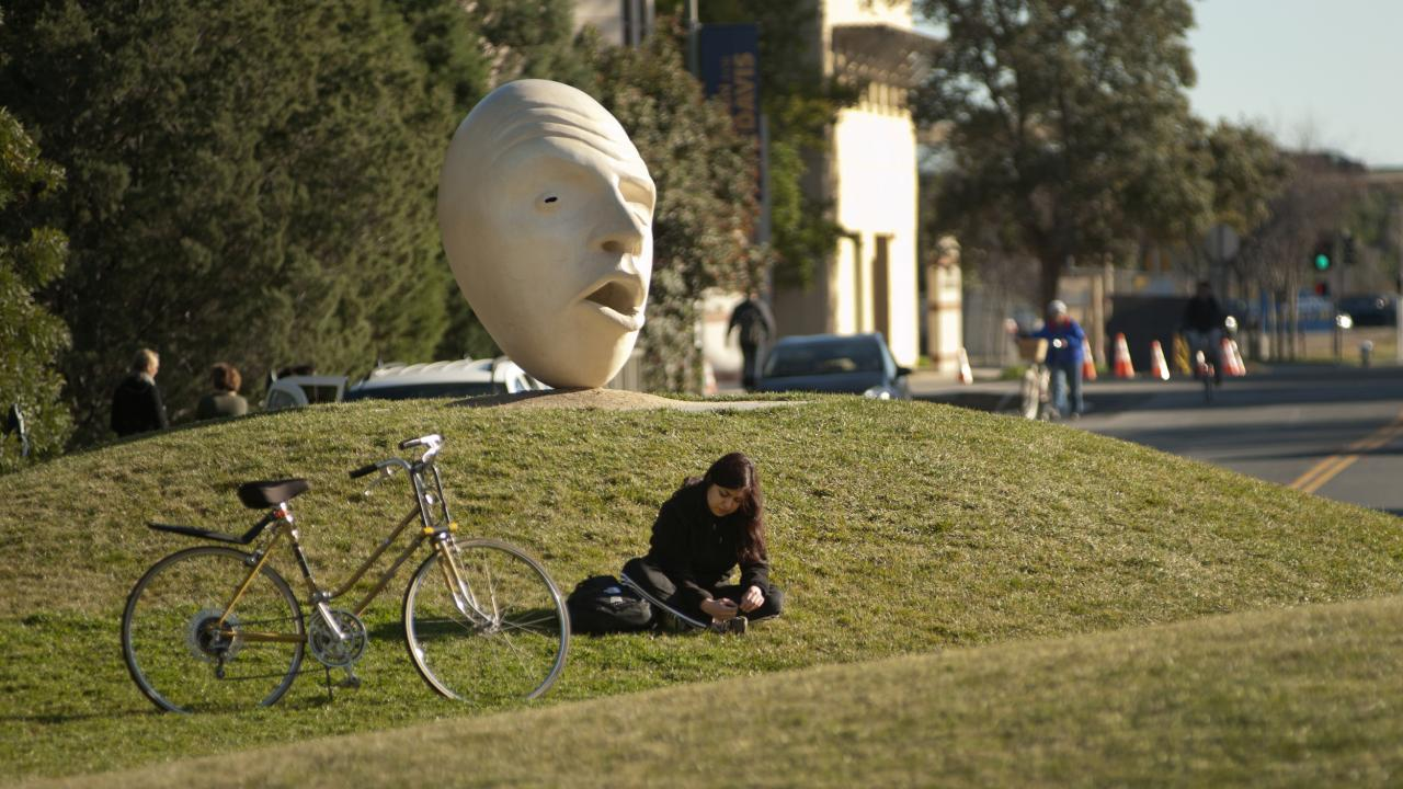 girl reading on sunny lawn next to her bike and UC Davis egghead sculpture
