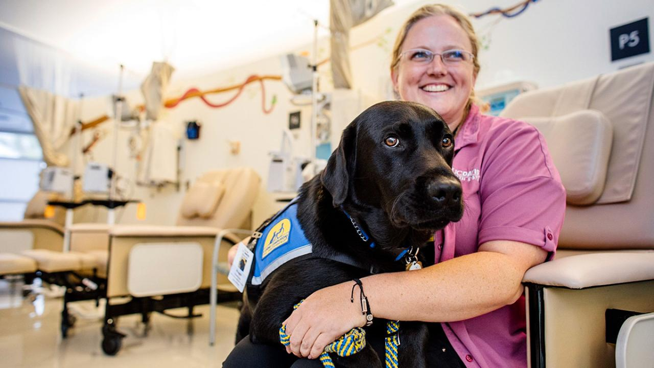 Jenny Belke sits in a medical office with Huggie, a black Labrador.