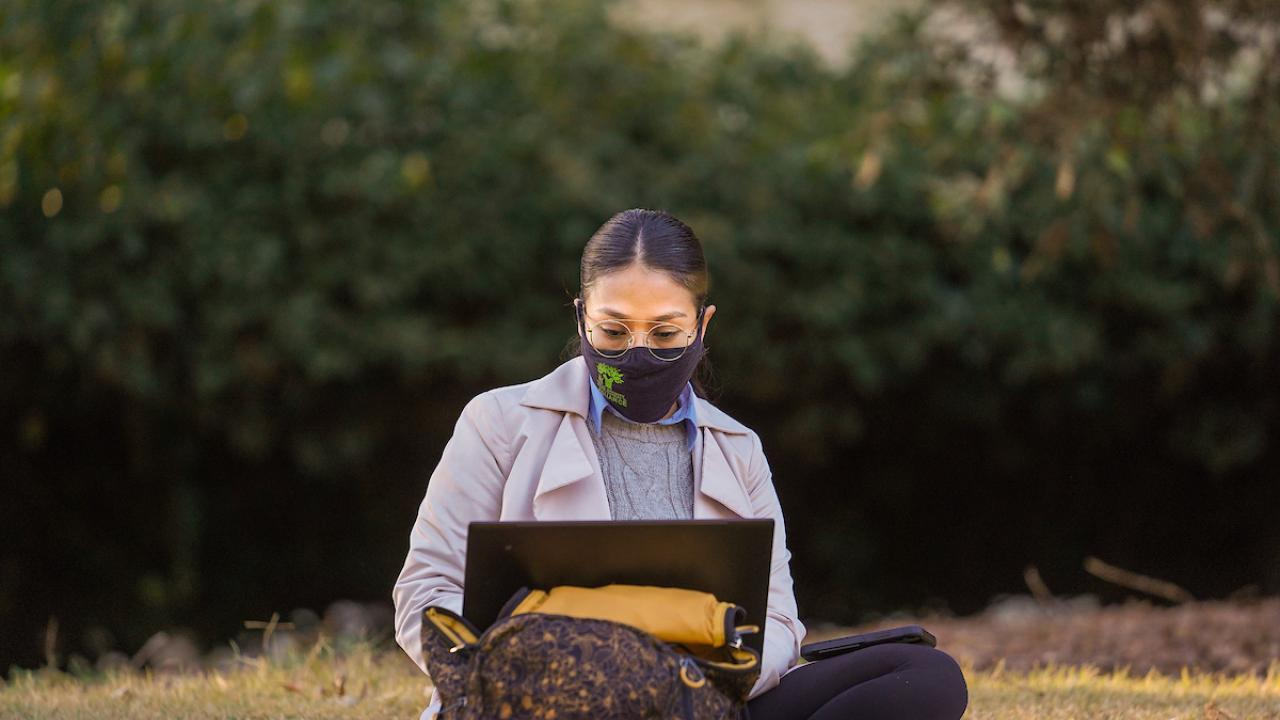 Student with face mask sits on ground while looking at an open laptop screen.