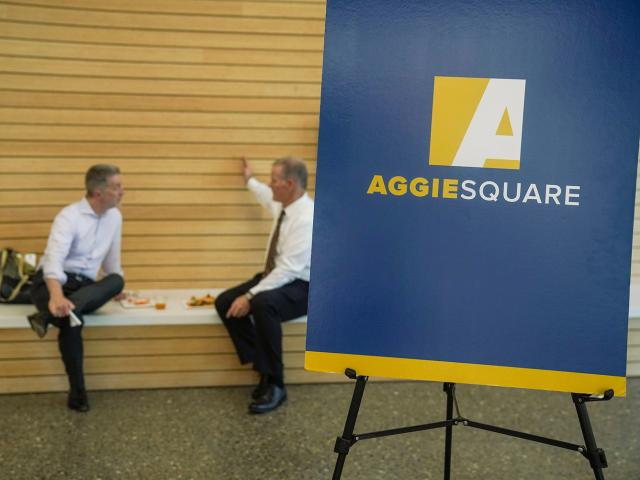 Blue and gold poster board on an easel with the words Aggie Square on it. Two men sitting down in the background.