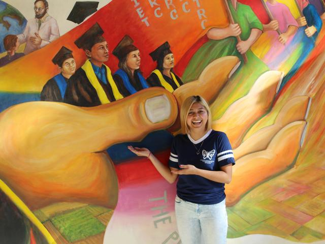 Estefania Sinay Pacheco poses with a mural.