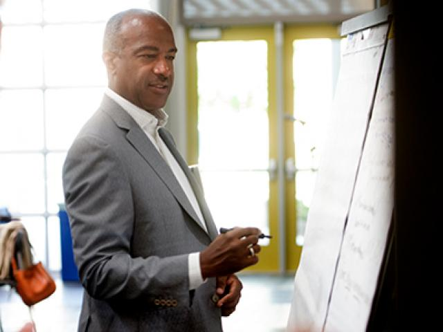Chancellor Gary S. May Brainstorms at a white board