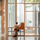 Two people sitting at separate desks spaced far apart in the library adjacent to the courtyard windows.