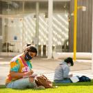 Two students wearing masks studying on lawn.